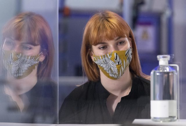 Lady wearing a mask looks at a display at the Our Future Planet exhibition at London's Science Museum