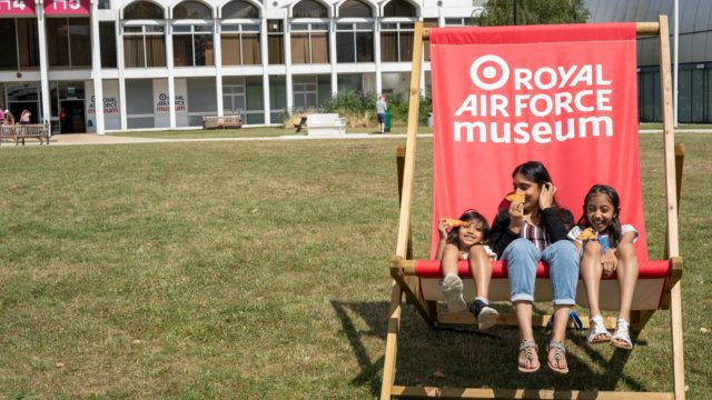 Family sit on a giant deckchair at RAF Museum London