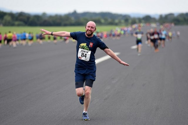 RAF Museum Spitfire 10K runner, runs with arms outstretched like an airplane