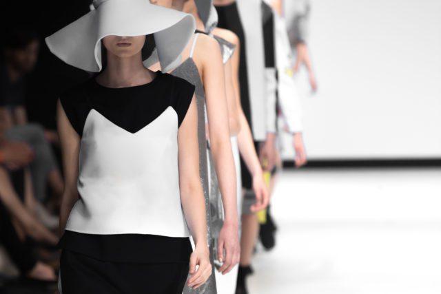Models wearing striking geometric clothing walk down the catwalk at London Fashion Week